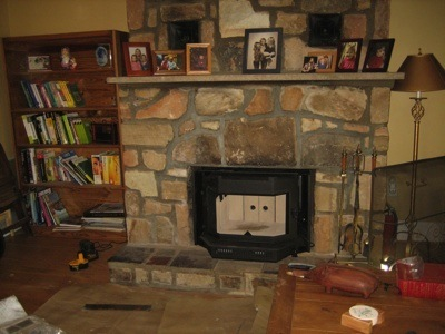 A black wood burning stove has been placed in the fireplace opening.
