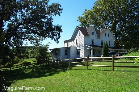 A backside perspective of a white farm house with a wrap around porch. There is green grass and a split rail fence around the house.