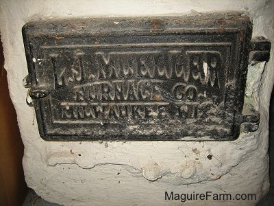 A black door in a cement wall that says 'Old Furnace Cover - L. J. Mueller Furnace Co. Milwaukee WI'