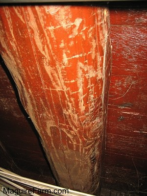 Close up - red colored old basement wooden beam with axe marks in the wood