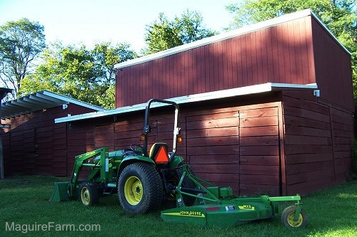 A John Deere tractor in front of the lower red barn